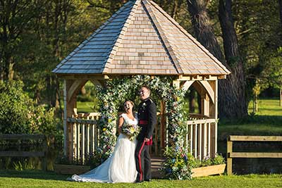 A wedding underneath an oak gazebo